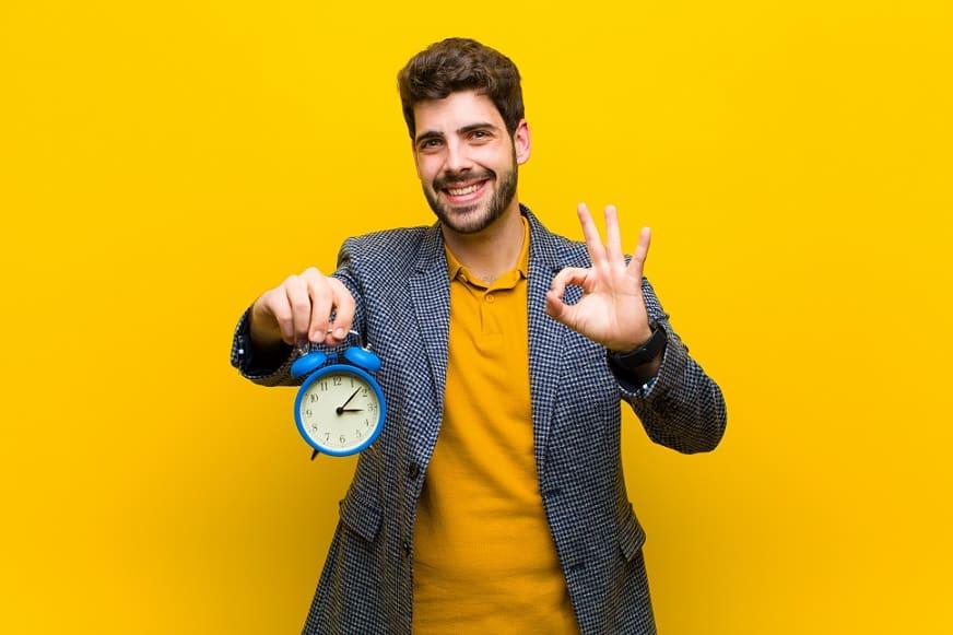 בחור צעיר עם ג'קט אפור מחזיק שעון ומודד זמן