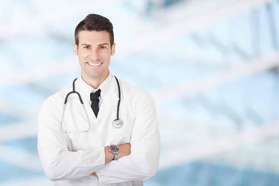 בחור צעיר עם חלוק של רופא משלב ידיים