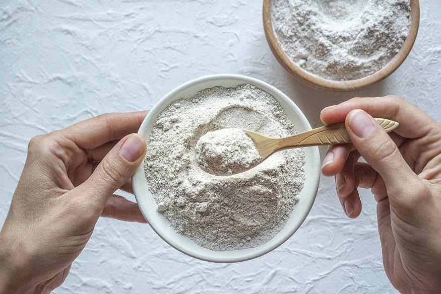 ידיים מערבבות אבקת חלבון בתוך קערה קטנה
