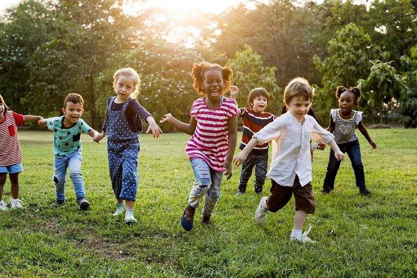 קבוצה של ילדים קטנים רצים בפארק על דשא ירוק