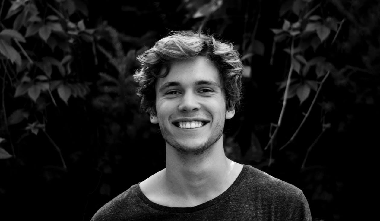 תמונת שחור ולבן של בחור צעיר שמחייך למצלמה
