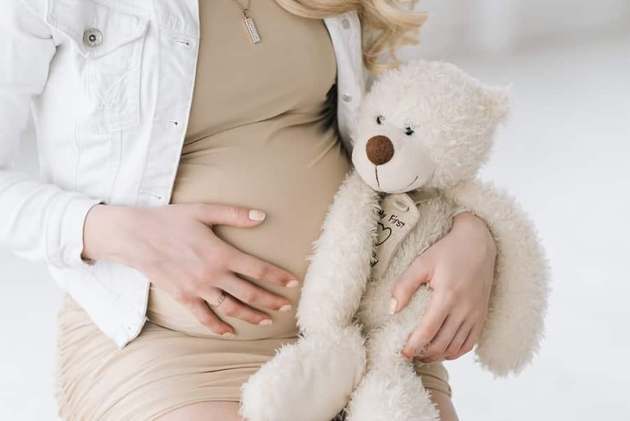 אישה בהריון מחזיקה את הבטן יחד עם בובה של דובי קטן