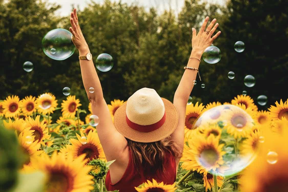 אישה בשדה של חמניות עם הידיים למעלה ובועות