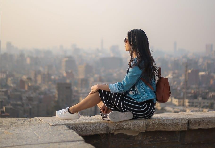 אישה יושבת על קצה גג הבניין ומסתכלת לשמיים