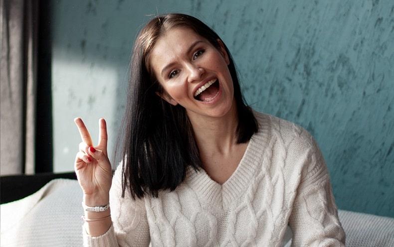 אישה עושה סימן של וי שלום עם היד
