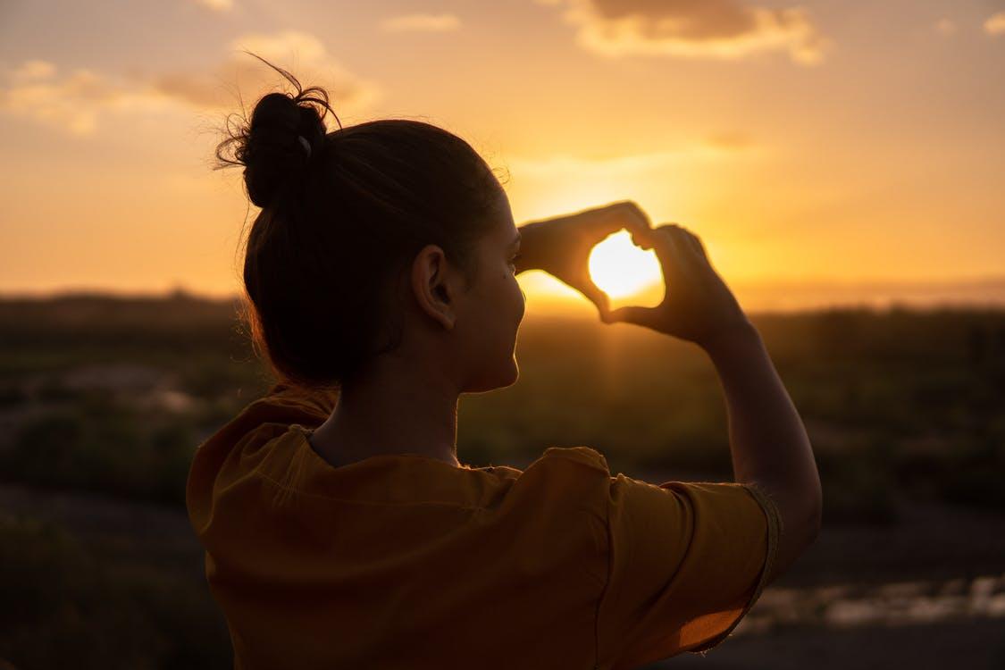 בחורה עושה סימן של לב ומכוונת אותו אל השמש