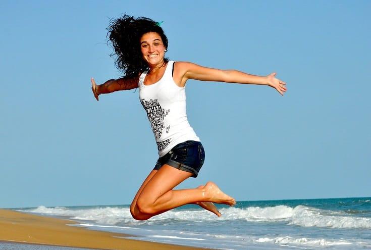 בחורה צעירה קופצת על חוף הים עם ידיים פתוחות
