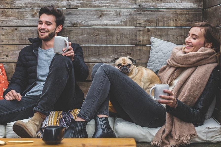 בחור ובחורה צעירים עם כלב יושבים בזולה ושותים חומצות אמינו BCAA בכוס