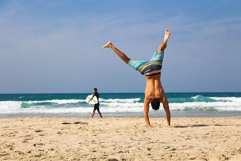 בחור צעיר עושה עמידת ידיים על חוף הים עם גולש שהולך ברקע