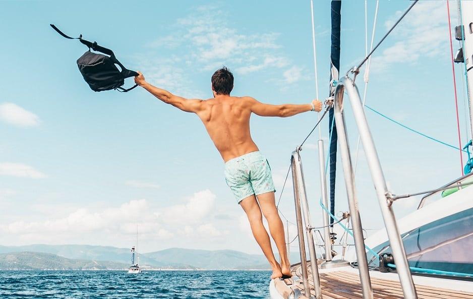 גבר מחזיק תיק ביד ונאחז במעקה של ספינה כדי לא ליפול למים