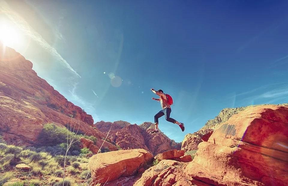 גבר קופץ בין דיונות במדבר על רקע השמיים