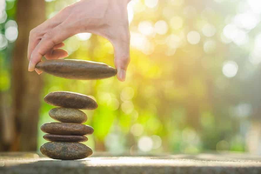 יד מניחה אבן גדולה על ערימת אבנים מאוזנת
