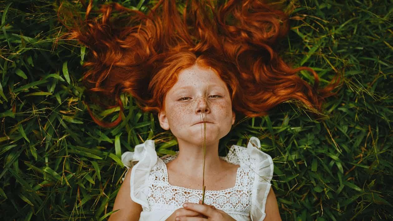 ילדה ג'ינג'ית שוכבת על הדשא ואוכלת חתיכת עשב
