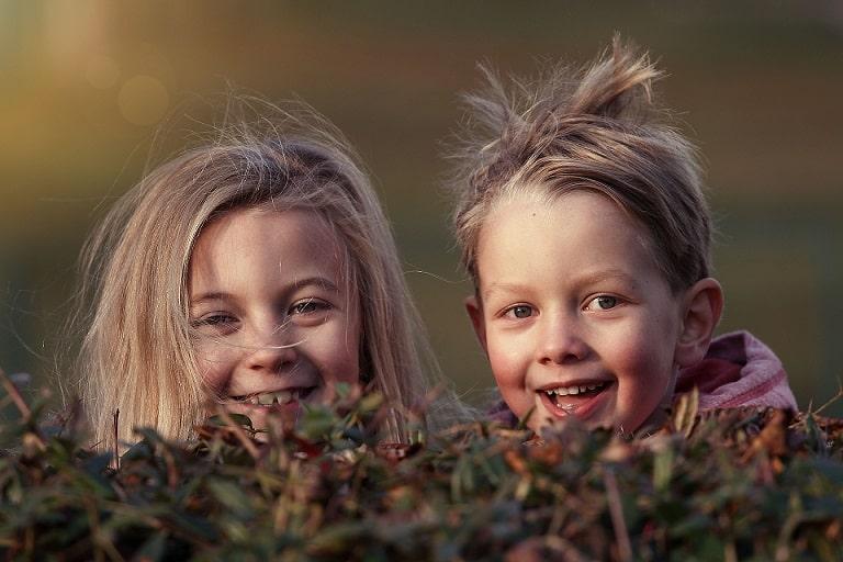 ילד וילדה מציצים מבין השיחים וצוחקים