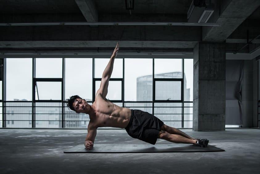 ספורטאי צעיר עושה תרגילים על מזרון בבניין נתוש