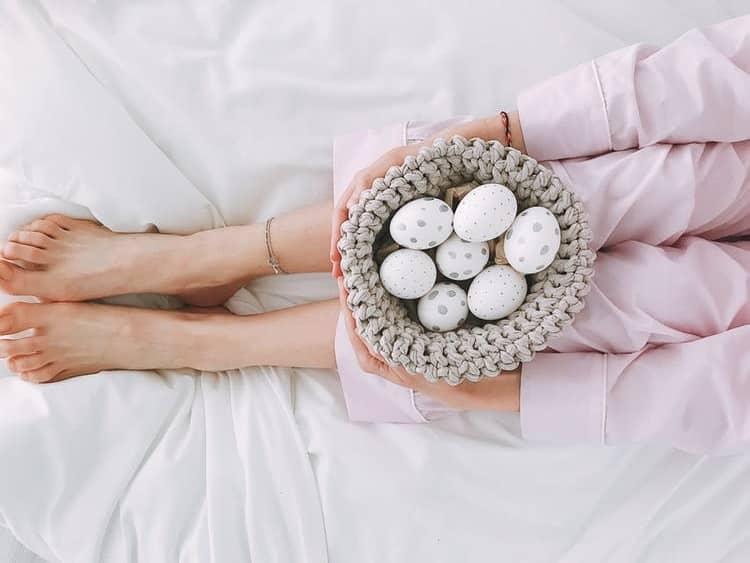 רגליים וידיים מחזיקות ביצים בצבעים שונים על המיטה