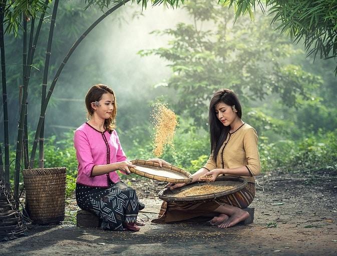 שני בחורות מקפיצות אורז בזמן ההכנה שלו
