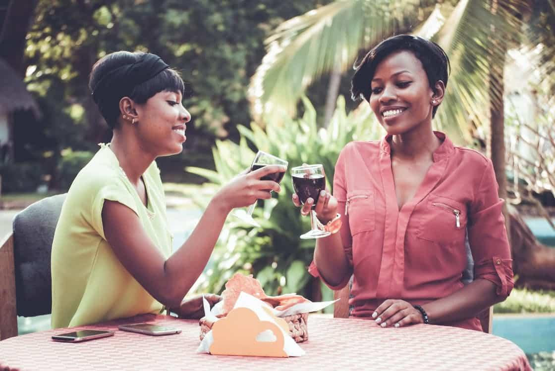 שני נשים שותות יין בחופשה עם עצי דקל ברקע