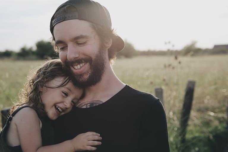 אבא עם כובע הפוך מחזיק את הבת הקטנה שלי בידיים ומחבק אותה