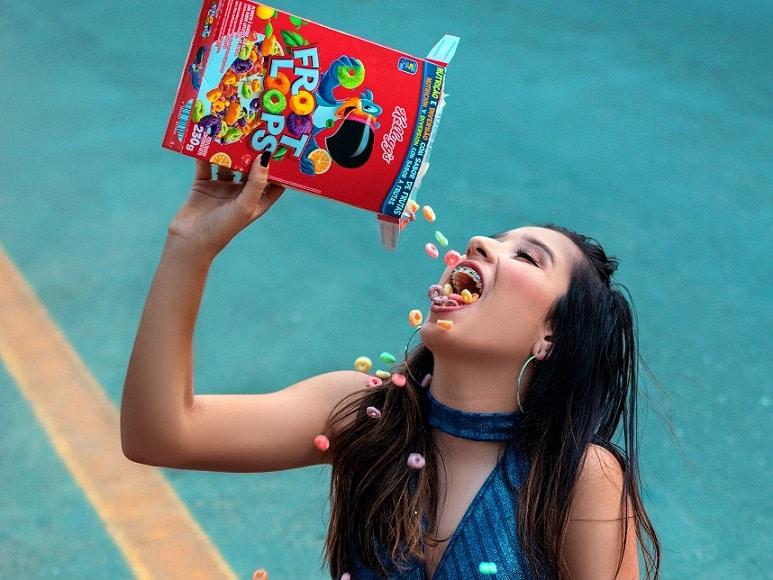 אישה עם גשר בשיניים שופכת לפה דגני בוקר צבעוניים
