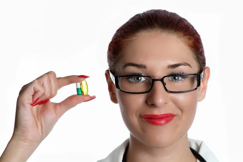 אישה עם משקפיים מחזיקה כמוסה ביד אילוסטרציה של מינון