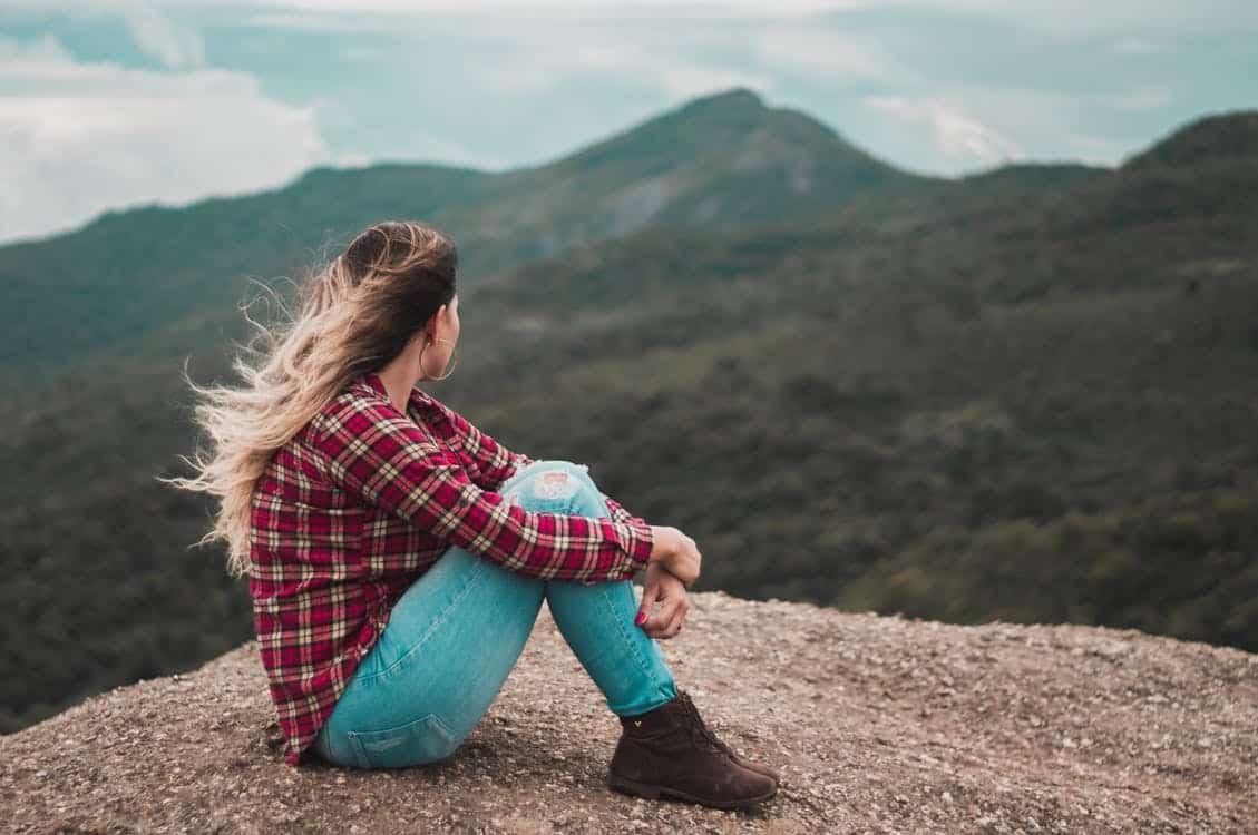 בחורה יושבת על פסגת של הר בצוק ומביטה אל עבר הר אחר