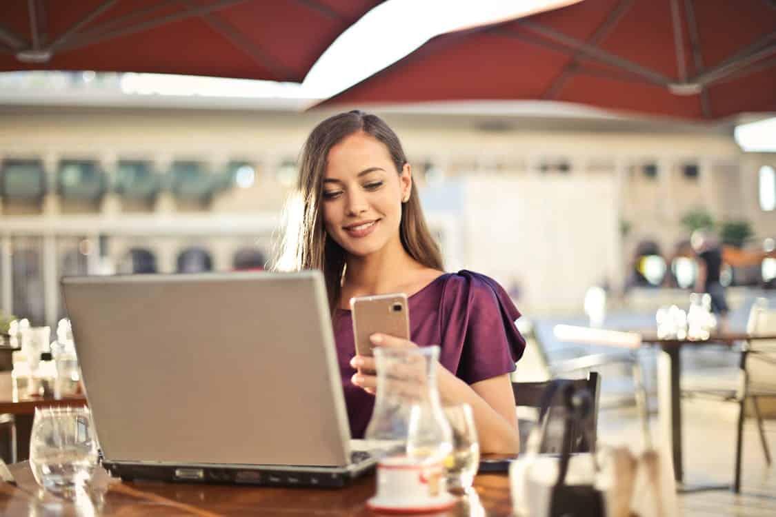 בחורה צעירה יושבת בבית קפה עם לפטופ ומסתכלת לתוך הסמארטפון שלה