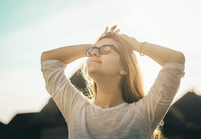 בחורה צעירה עומדת בשמש עוצמת עיניים ומטה את הראש למעלה