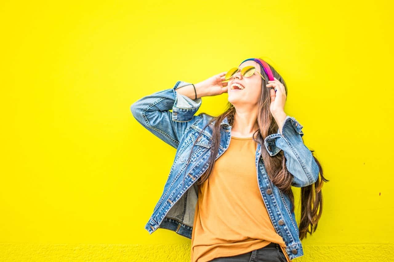 בחורה צעירה על רקע צהוב מסתכלת למעלה ומחייכת