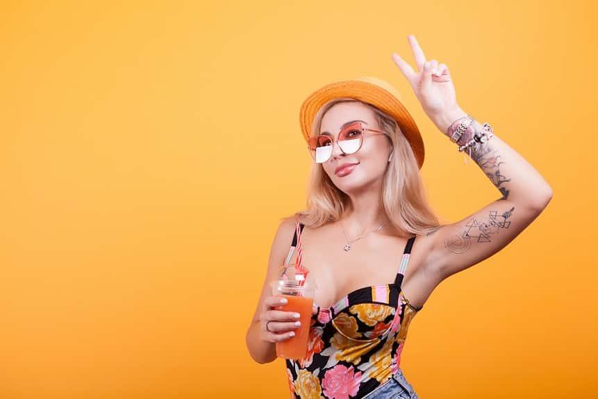 בחורה צעירה עם כובע קיץ ומשקה קל ביד עושה פוזות למצלמה