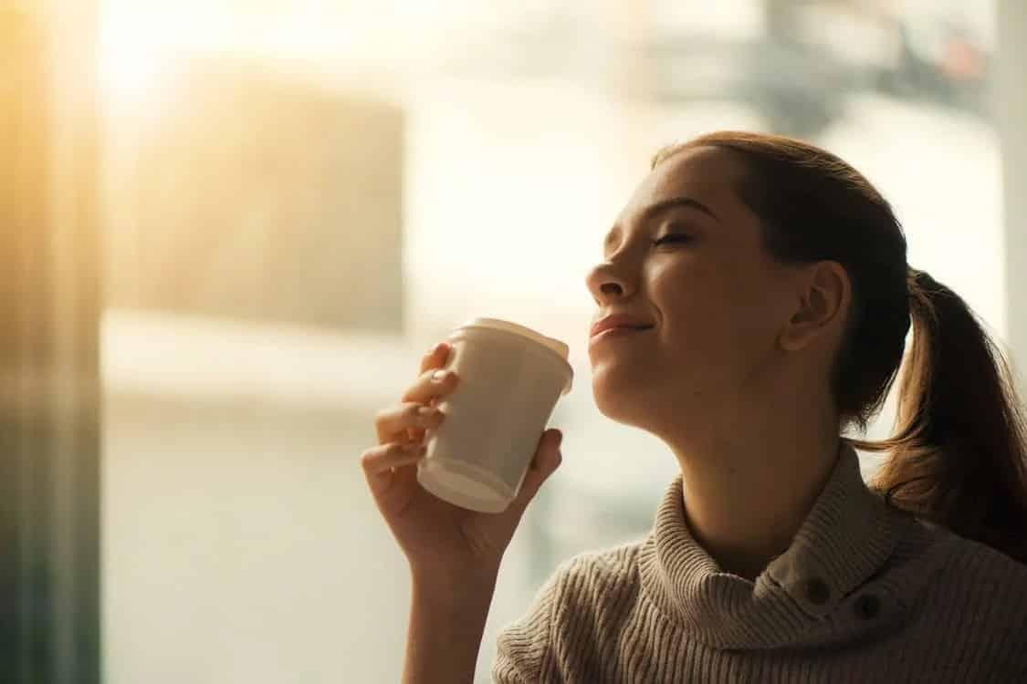 בחורה צעירה עם קוקו עוצמת עיניים ומתענגת על תה חם