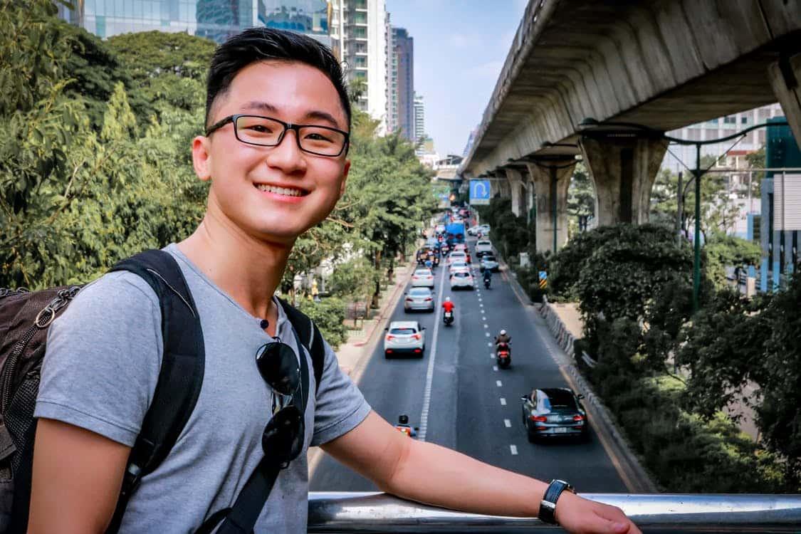 בחור אסייתי צעיר מצתלם על רקע של כביש עם מכוניות