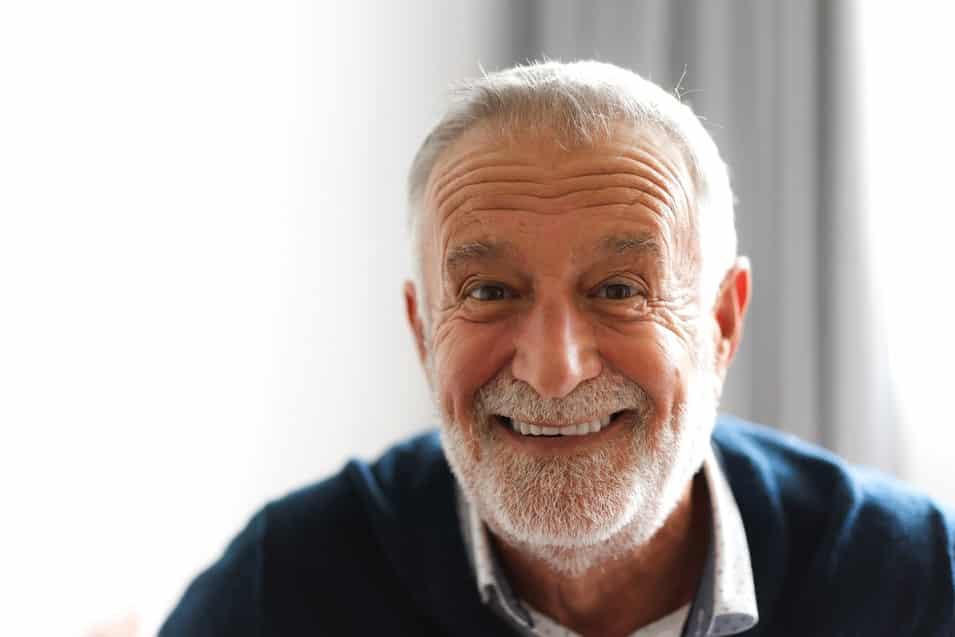 גבר מבוגר עם שיער לבן מסתכל למצלמה ומחייך