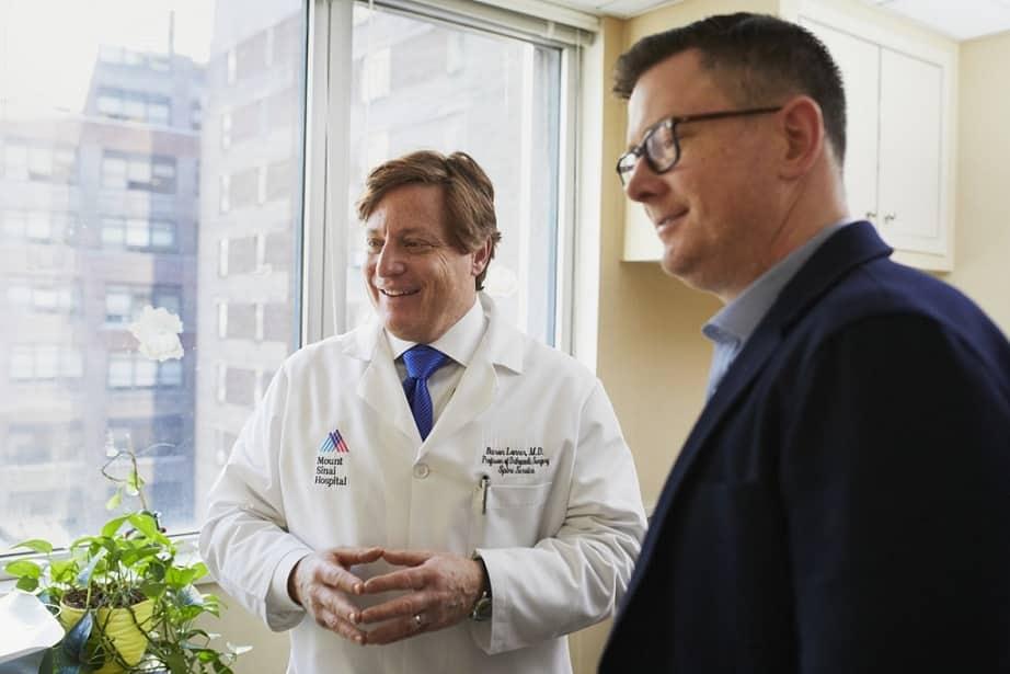 גבר עומד ליד רופא ושניהם מסתכלים לצד ימין