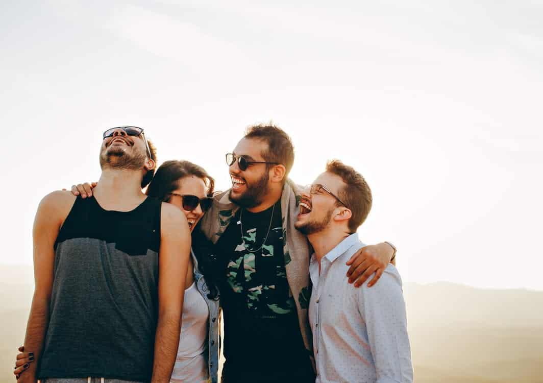 חבורה של חברים צעירים מתחבקים וצוחקים