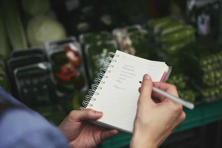 יד עוברת על רשימה של מוצרים שכתובים במחברת