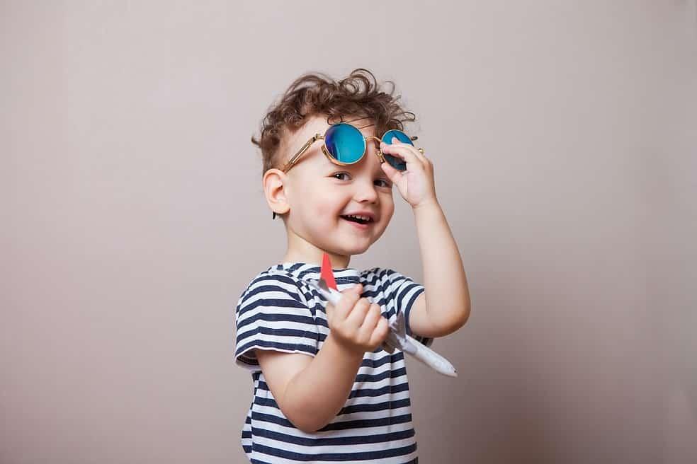 ילד קטן וחמוד מחזיק צעצוע של מטוס