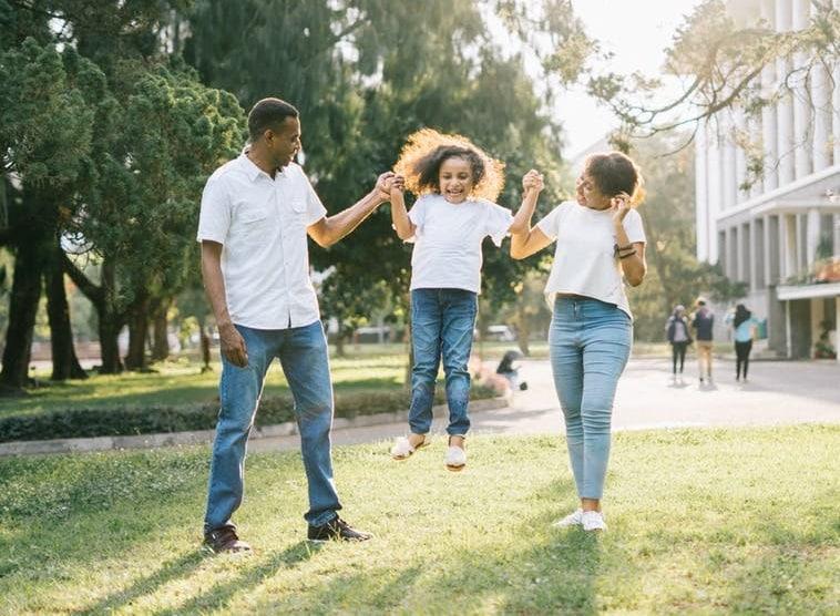 משפחה אבא אמא ובת מבלים בפארק ומשחקים בקפיצה