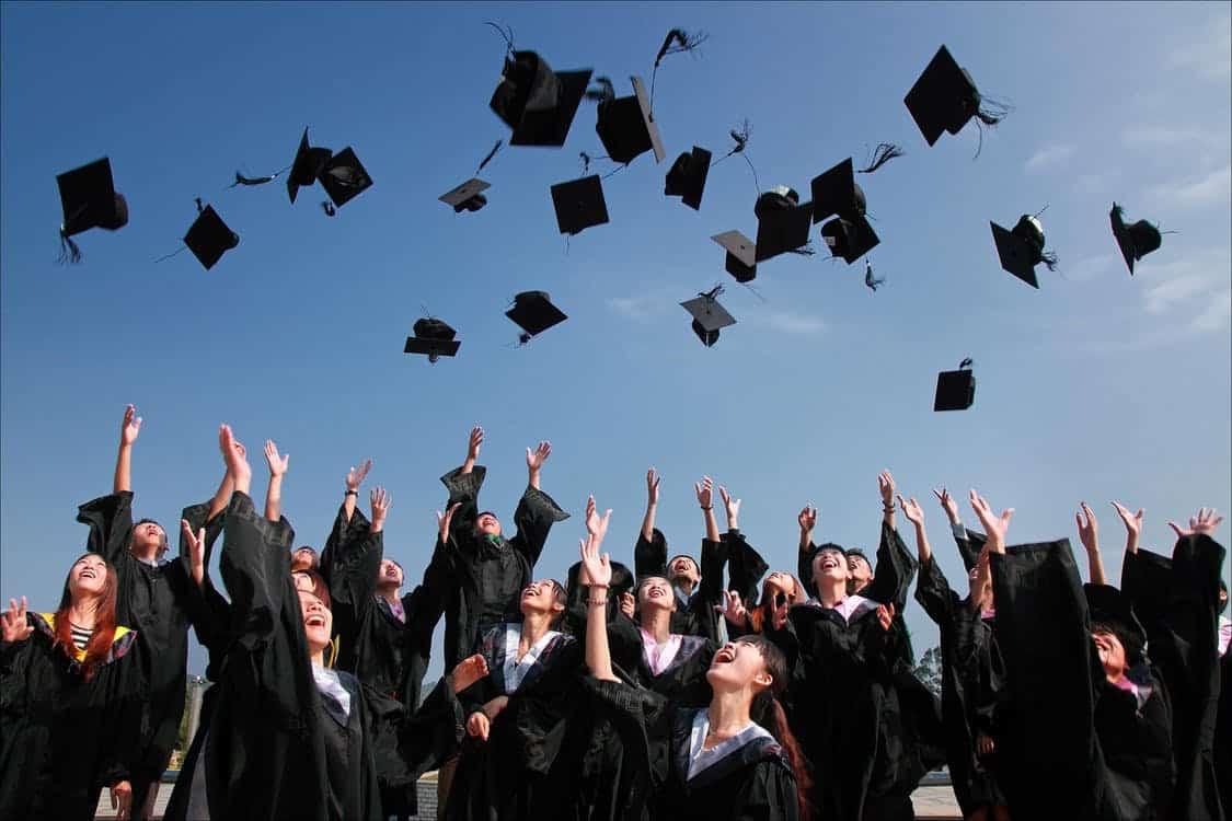 סטודנטים שמחים שזורקים כובעים שחורים באוויר