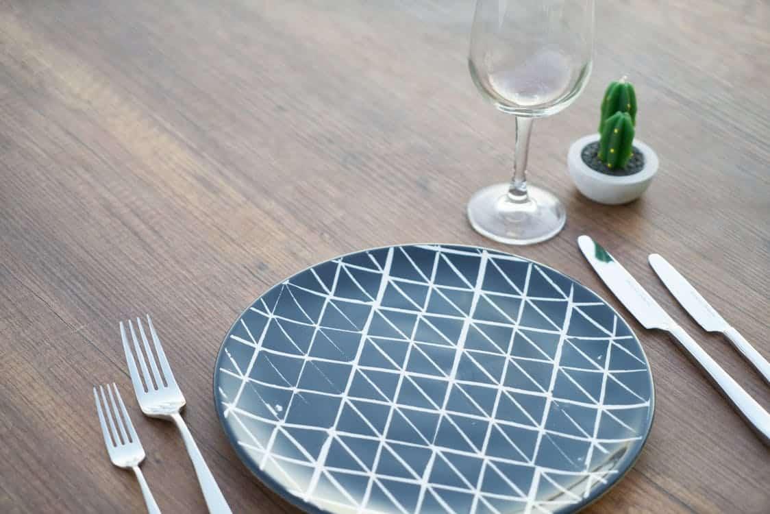 צלחת ריקה עם כלי אוכל על שולחן מעץ