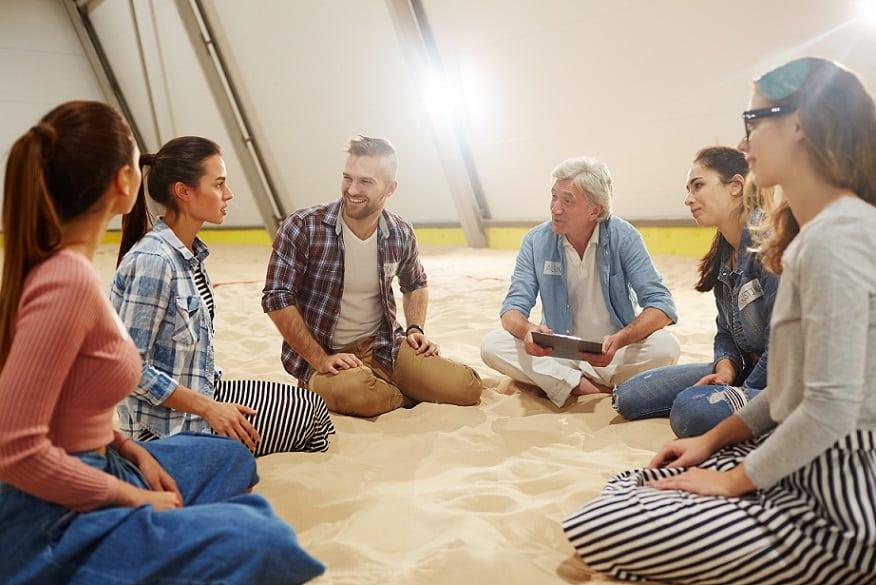 קבוצה של אנשים צעירים יושבים באוהל ושואלים שאלות אחד את השני