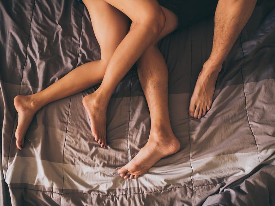 רגליים של זוג ששוכב במיטה על מצעים אפורים