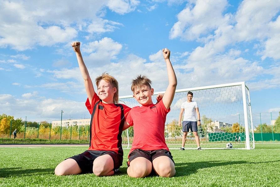 שני חברים עם מדי כדורגל בצבע אדום עומדים על הברכיים ומריעים לעצמם