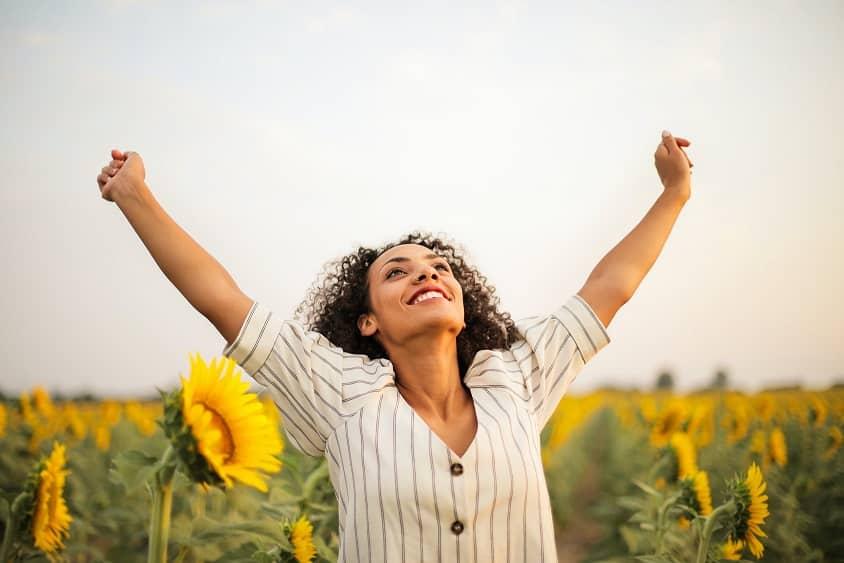 אישה עם תלתלים מרימה את הידיים שלה ומביטה לשמיים בתנועת ניצחון