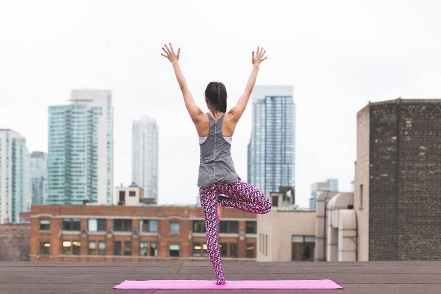 בחורה צעירה עושה יוגה על המרפסת של הבניין שלה
