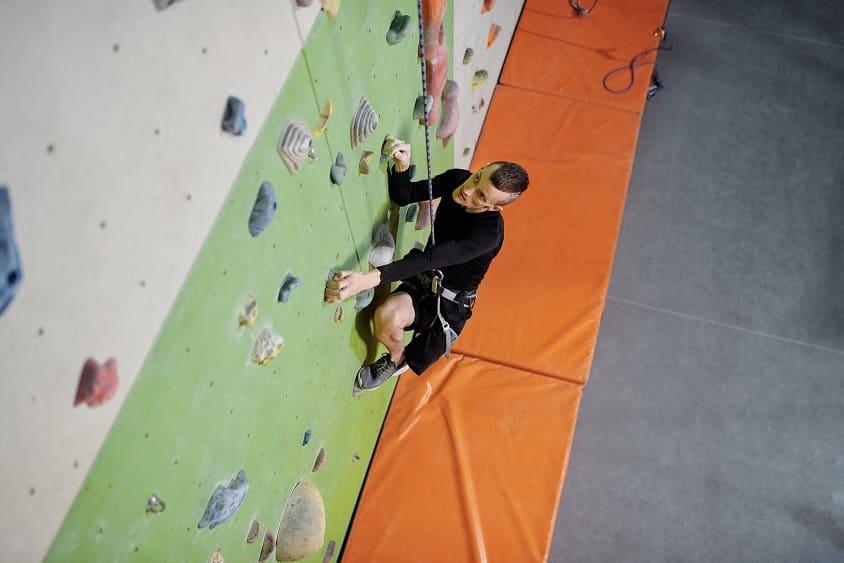 בחור צעיר מטפס על קיר טיפוס ומצליח להתגבר על המכשולים שבדרך