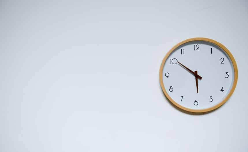 שעון מחוגים רגיל תלוי על קיר בצבע לבן ומראה את השעה