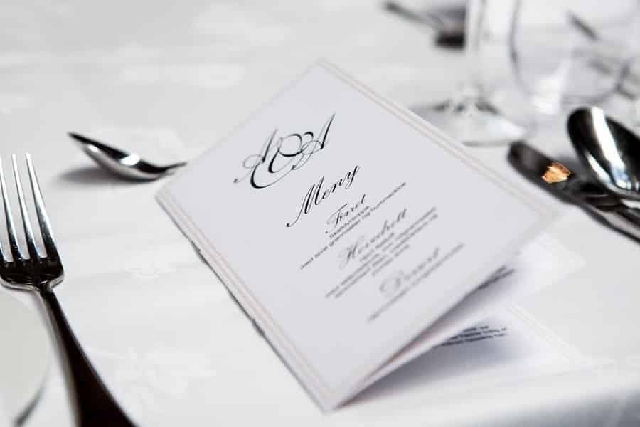 תפריט של מסעדה בצבע לבן מונח על מפת שולחן ליד כלי אוכל שונים