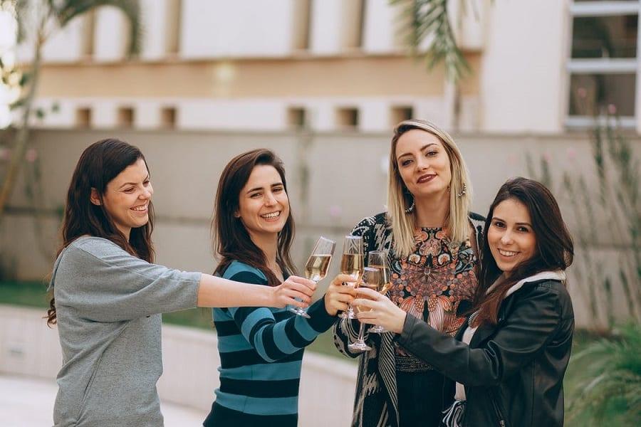 4 חברות מחזיקות כוס שמפניה ביד ומסתכלות ביחד למצלמה עם חיוך