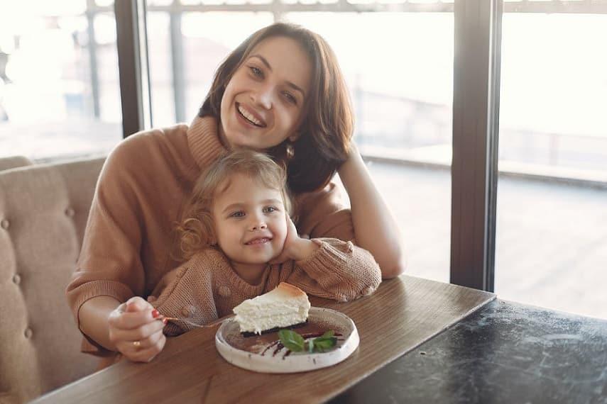 אמא ובת יושבות בדיינר אוכלות עוגת גבינה ומחייכות למסך